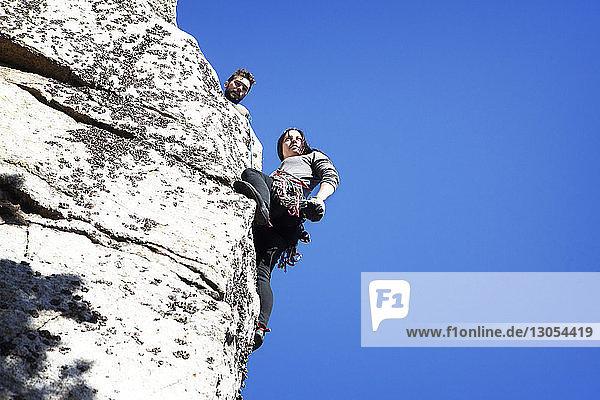 Tiefwinkelansicht eines Mannes  der seine Freundin beim Abseilen gegen den klaren blauen Himmel betrachtet