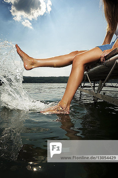 Low section of young woman splashing water while sitting on jetty over lake