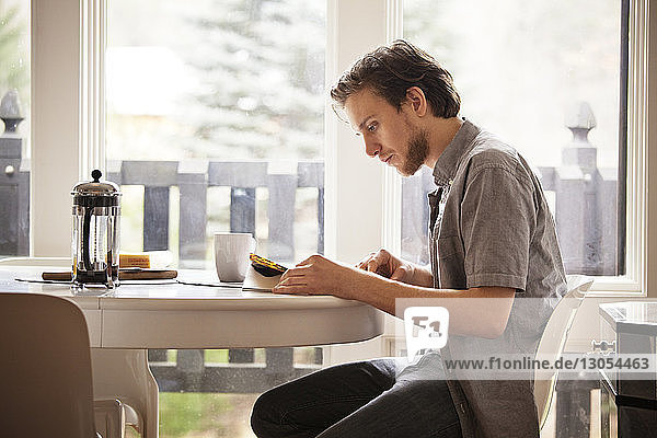 Man reading magazine while sitting on chair by breakfast table at home