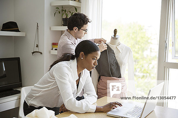 Female working on laptop while colleague pinning dress on model in studio