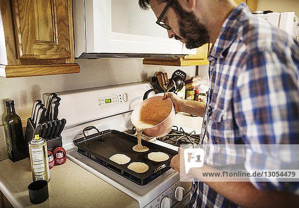 Man pouring pan cake batter on baking sheet at home