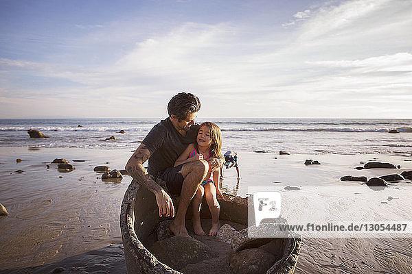Vater und Tochter sitzen bei Sonnenuntergang auf einem Betonrohr am Strand