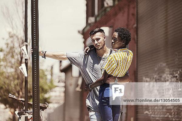 Trendiges Paar steht am Straßenschild auf dem Bürgersteig