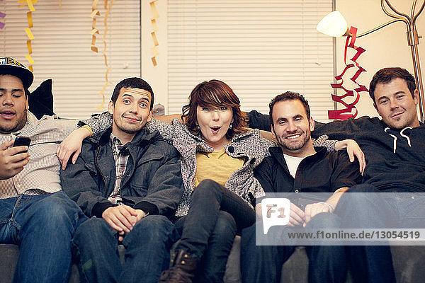Porträt von fröhlichen Freunden  die zu Hause auf dem Sofa im Wohnzimmer sitzen