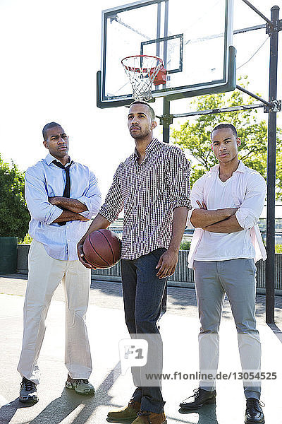 Confident man holding basketball while standing with friends in court