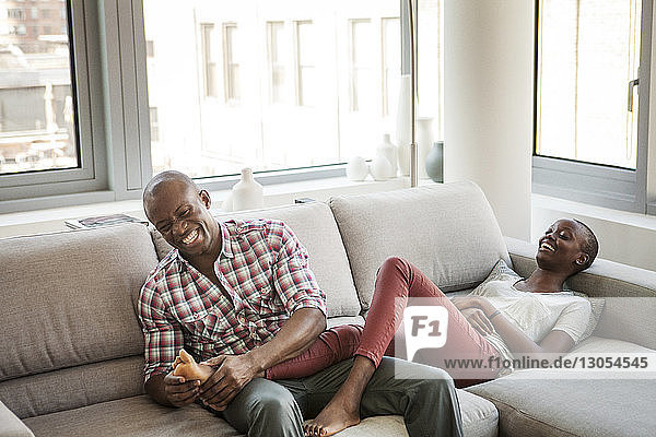 Cheerful man holding toe of woman lying on sofa at home