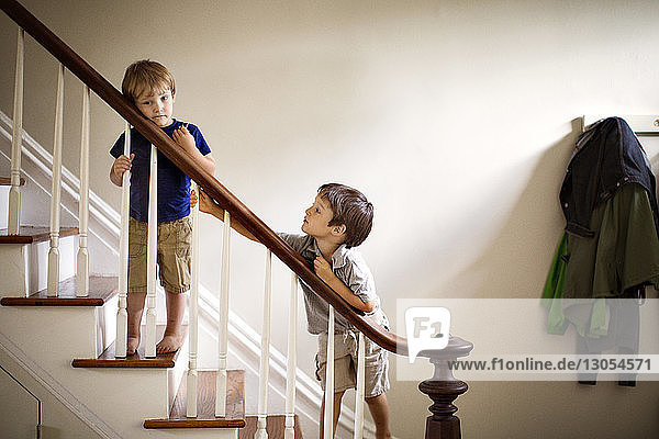 Brothers standing at railing of staircase in house
