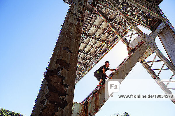 Low angle view of man climbing bridge