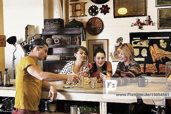 Männlicher Besitzer schenkt Getränke ein  während die Familie im Café ein Smartphone benutzt