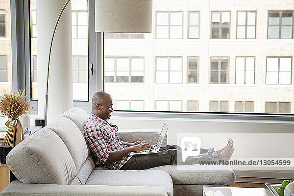 Side view of man using laptop computer while sitting on sofa at home