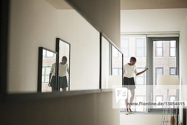 Woman looking down while standing on window sill