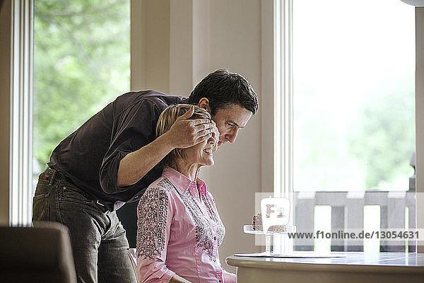 Mann bedeckt Frau die Augen  während er zu Hause Geburtstag feiert
