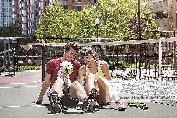 Glückliches Paar sitzt mit Hund auf dem Tennisplatz