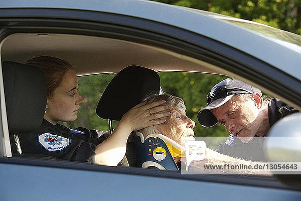 Sanitäter legen dem Patienten im Auto eine Halskrause an