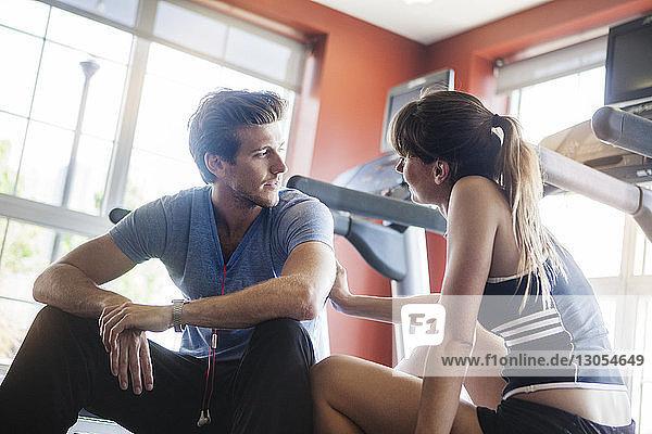 Paar  das im Fitnessstudio auf dem Laufband sitzt