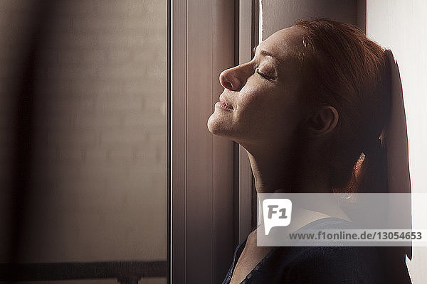Close-up of woman with eyes closed leaning on wall at home