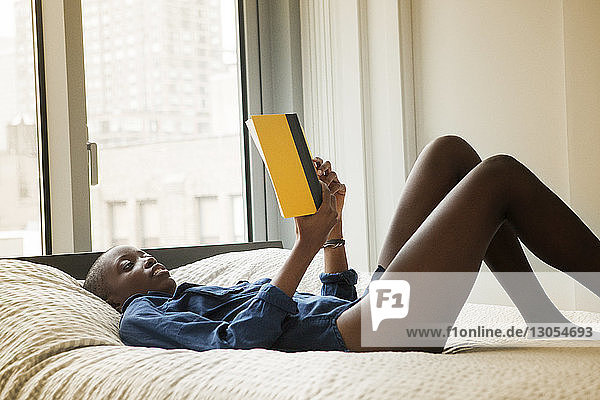 Side view of woman reading book while lying on bed at home