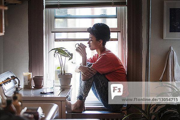 Seitenansicht einer Frau  die trinkt  während sie zu Hause auf dem Fensterbrett sitzt