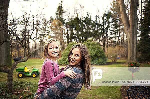 Portrait of happy mother carrying daughter in backyard