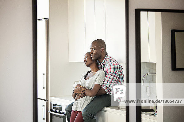 Man embracing woman while sitting on kitchen counter at home