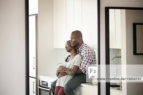 Mann umarmt Frau  während er zu Hause auf dem Küchentisch sitzt