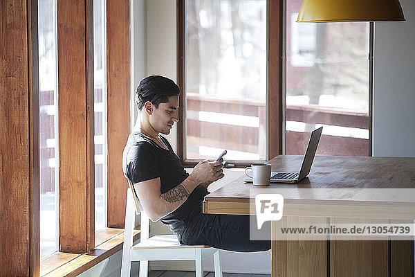 Man using smart phone while sitting on chair by table at home