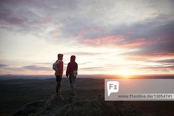 Rückansicht von Wanderern  die bei Sonnenuntergang auf einer Klippe gegen den Himmel stehen