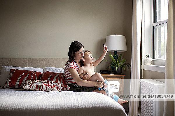 Mutter kleidet verspielten Sohn an  während er auf dem Bett sitzt