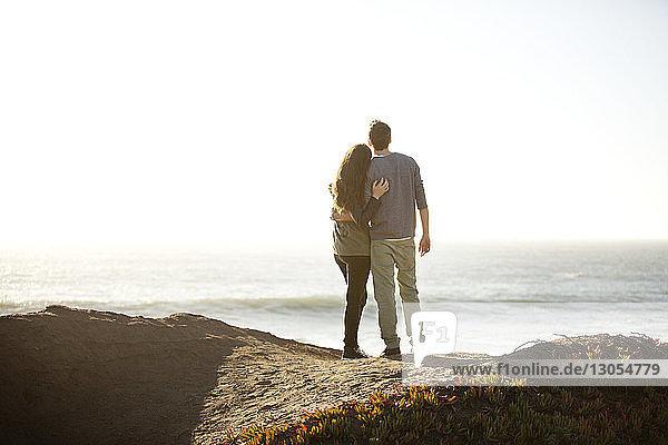 Rückansicht eines Paares  das sich am Ufer vor klarem Himmel umarmt