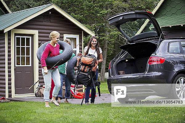 Happy friends loading car for camping