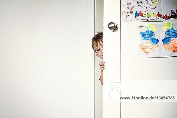 Portrait of boy behind door at home