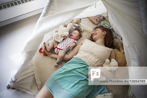 High angle view of mother and daughter lying in tent at home
