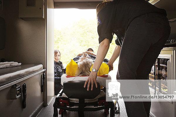 Paramedics pushing hospital gurney in ambulance