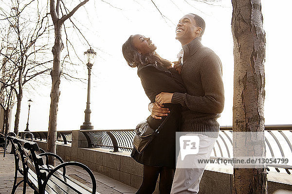 Cheerful couple embracing by railing against sky on sunny day