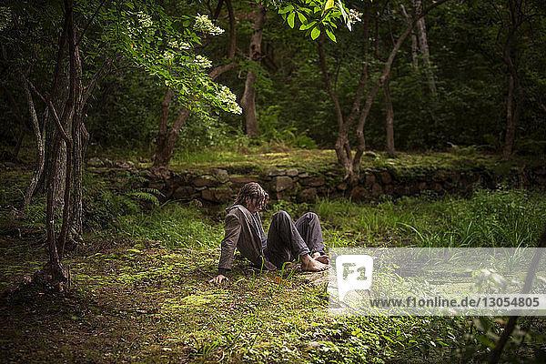 Mann sitzt auf Feld im Wald