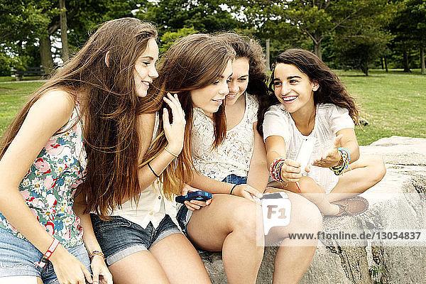 Teenager-Mädchen zeigt Freundinnen ein Handy  während sie im Park sitzen