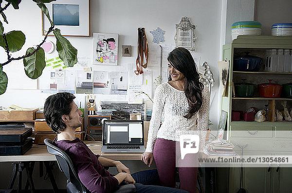 Junges Paar schaut zu Hause am Tisch von Angesicht zu Angesicht