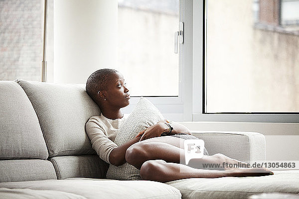 Woman looking away while relaxing on sofa at home