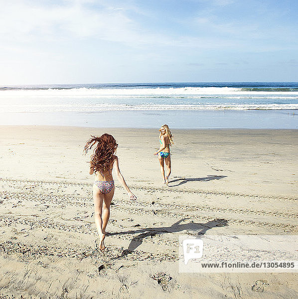 Happy friends in bikini running on shore at beach