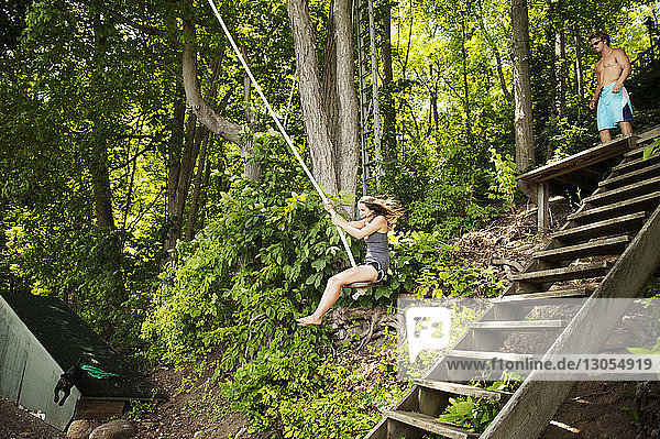 Cheerful woman swinging on rope in forest