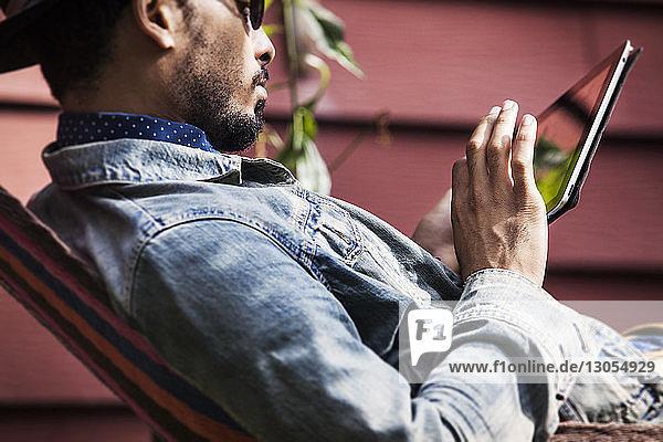 Mann benutzt Tablet-Computer  während er sich in der Hängematte entspannt