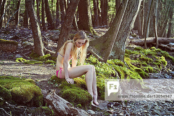 Full length of woman sitting on riverbank in forest