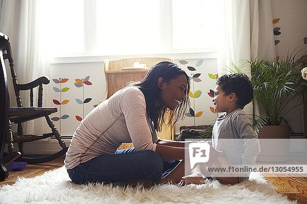Seitenansicht einer Mutter  die mit ihrem Sohn spielt  während sie zu Hause auf dem Teppich sitzt