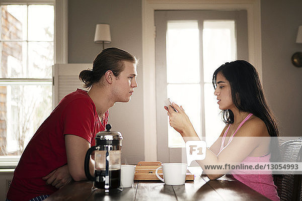 Man looking at woman using mobile phone at table