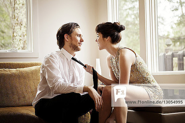 Woman pulling man's necktie while sitting at home