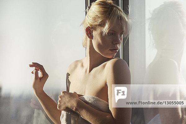Überraschte  in ein Handtuch gewickelte Frau schaut über die Schulter  während sie am Fenster steht