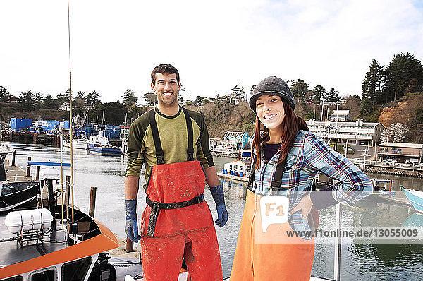 Porträt eines lächelnden Mannes und einer lächelnden Frau  die auf einem Fischerboot stehen