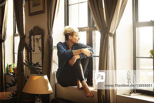 Frau schaut weg  während sie zu Hause am Fensterbrett sitzt