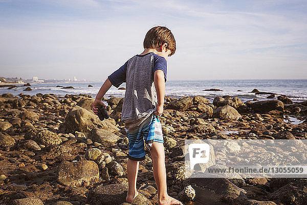 Rückansicht eines Jungen mit Fernglas  der am Strand auf Felsen läuft