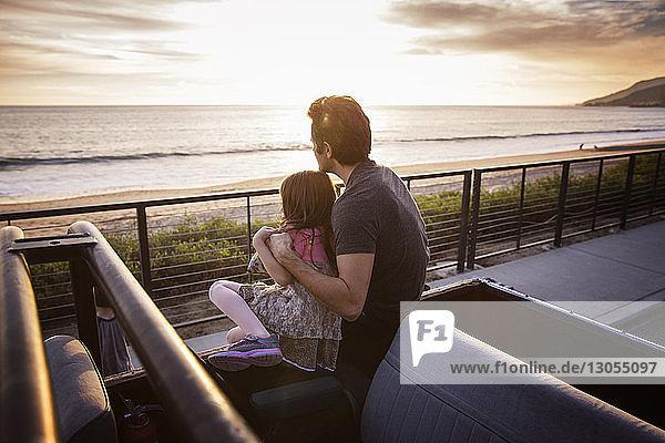 Vater und Tochter beim Anblick des Sonnenuntergangs